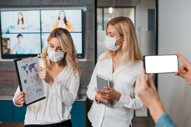 Schöne geschäftsfrauen, die medizinische masken tragen