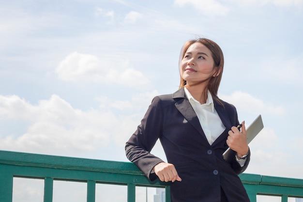 Schöne geschäftsführerfrau, die an erfolgsarbeit lächelt und denkt.