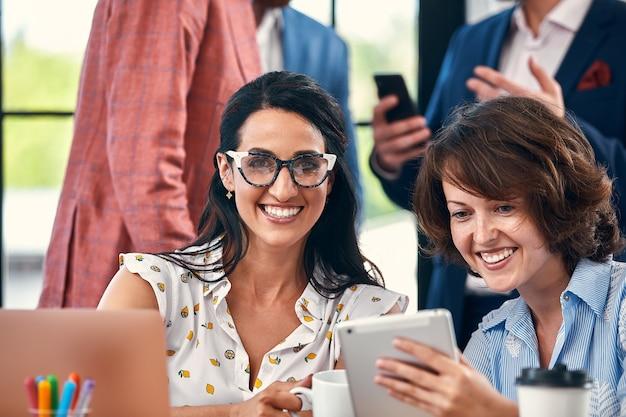 Schöne geschäftsleute benutzen geräte, sprechen und lächeln während der konferenz im büro.
