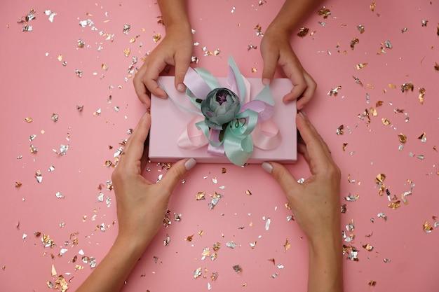 Schöne geschenkbox auf festlichem rosa, mit den händen des kindes und der mutter