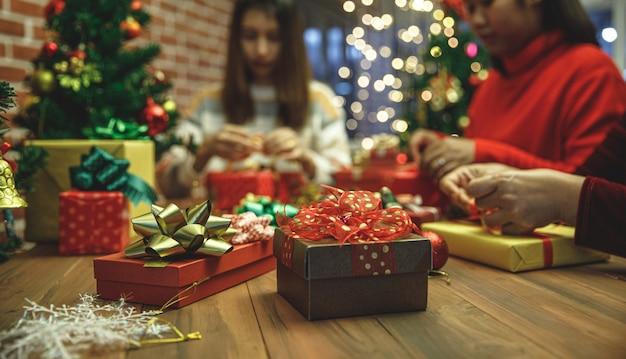 Schöne geschenkbox auf holztisch, dekoriert mit buntem, charmantem bogen. leute, die es als weihnachtsgeschenk für eine faszinierende familienfeier im winterurlaub verpacken. fügen sie etwas rauschen hinzu, um das bild im vintage-stil anzupassen.