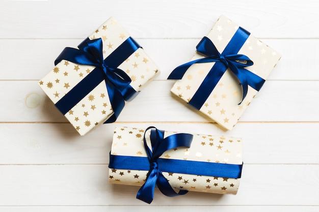 Schöne geschenkbox ein farbiger bogen auf dem weißen holztisch. draufsicht mit exemplar. weihnachten
