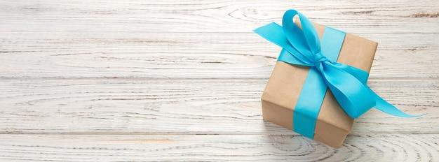 Schöne geschenkbox mit einem blauen bogen auf dem weißen holztisch.