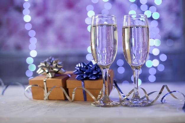 Schöne geschenkbox mit einer schleife mit gläsern champagner auf einem bokeh-hintergrund für das neue jahr weihnachten und geburtstag