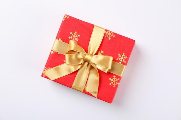 Schöne geschenkbox mit goldener schleife auf weißem hintergrund, platz für text