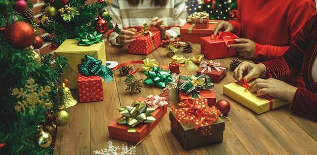 Schöne geschenkbox verpackt und verpackt von einer familiengruppe von frauen auf pullover mit buntem papier, band, charmanter schleife zum dekorieren des luxus-weihnachtsbaums für eine glückliche winterparty-vorbereitung im dezember