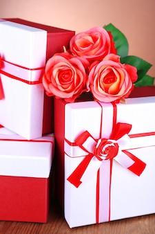 Schöne geschenkboxen mit blumen auf dem tisch auf braunem hintergrund