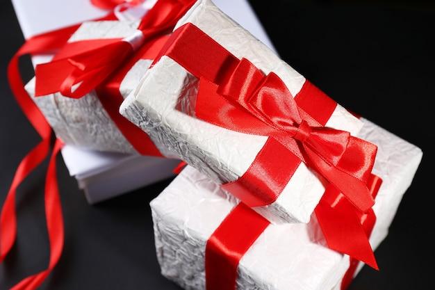 Schöne geschenke mit roten bändern, auf dunklem hintergrund