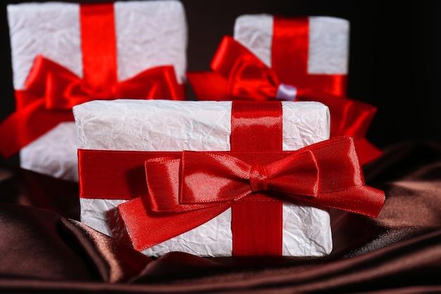 Schöne geschenke mit roten bändern auf seide, auf dunklem hintergrund