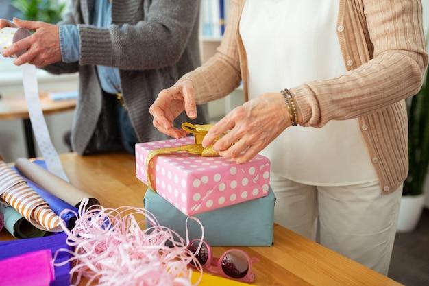 Schöne geschenke. nahaufnahme von zwei geschenkboxen, die auf dem tisch vor einer angenehmen alten frau stehen