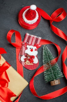 Schöne geschenke weihnachten socke weihnachtsbaum weihnachtsmann hut auf dunklem hintergrund