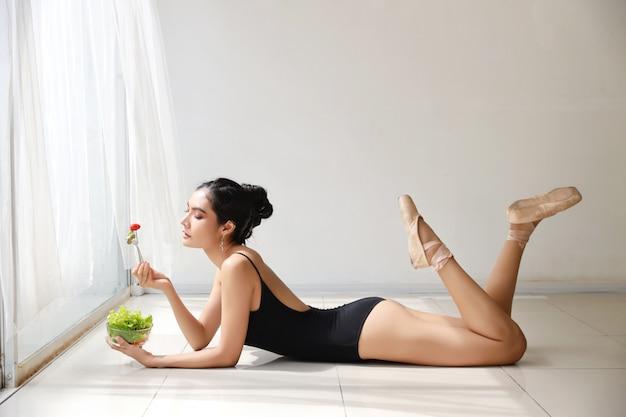 Schöne gesunde asiatische junge frau, die salat isst, nachdem ballett beim sich hinlegen ausgebildet worden ist
