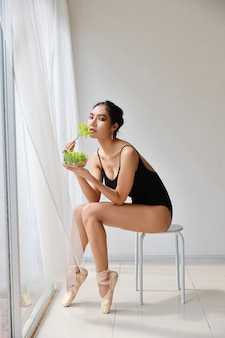 Schöne gesunde asiatische junge frau in voller länge, die salat nach dem training des balletts beim sitzen isst