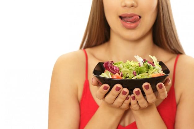 Schöne gesunde frau, die schüssel salat hält