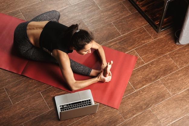 Schöne gesunde frau, die yogaübungen beim sitzen auf einer fitnessmatte zu hause, mit laptop-computer, dehnen tut