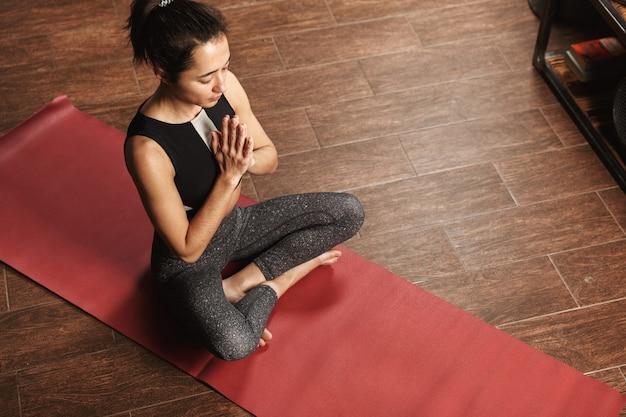 Schöne gesunde frau, die yogaübungen beim sitzen auf einer fitnessmatte zu hause tut