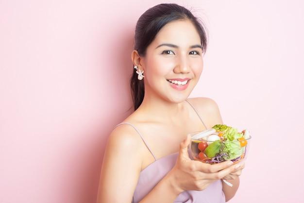 Schöne gesunde junge frau, die salat auf rosa hintergrund isst