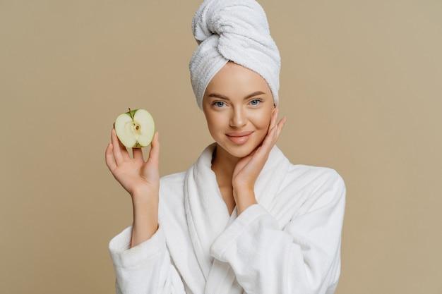 Schöne gesunde junge frau posiert mit badetuch auf dem kopf im morgenmantel gekleidet hält die hälfte des apfels