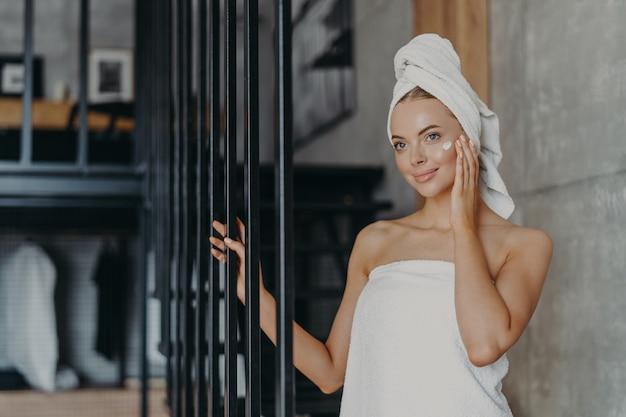 Schöne gesunde junge frau trägt gesichtscreme auf teint auf