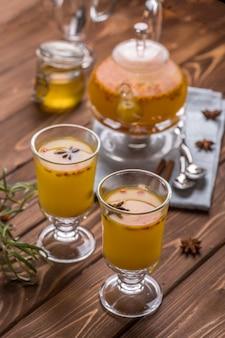 Schöne glas-teekanne mit orangefarbenem sanddorn-tee.