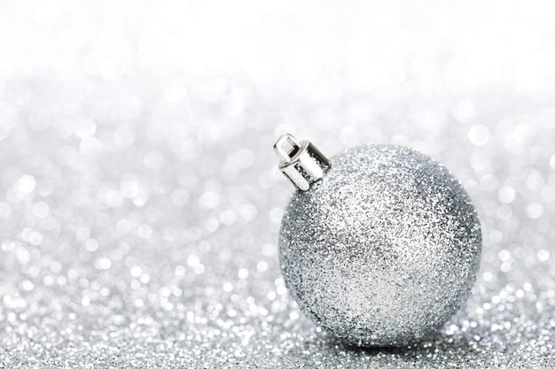 Schöne glitter weihnachtskugel nahaufnahme auf silbernem glitzer hintergrund