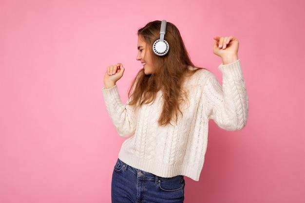 Schöne glücklich lächelnde junge brünette lockige frau mit weißem pullover isoliert auf rosa hintergrundwand mit weißen bluetooth-kopfhörern, die coole musik hört, die zur seite schaut und sich bewegt.