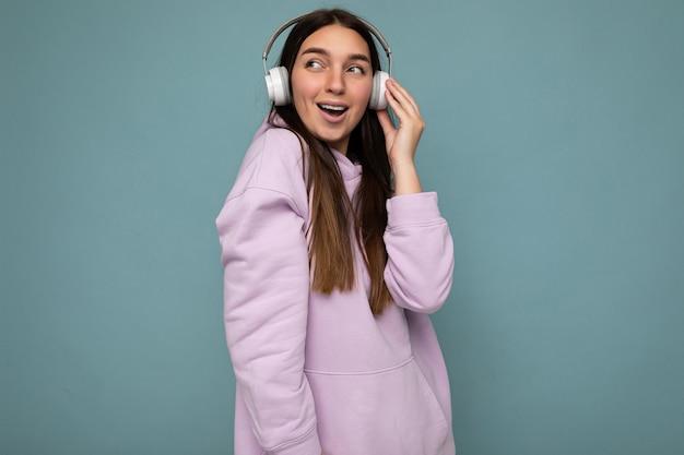 Schöne glücklich lächelnde junge brünette weibliche person mit hellviolettem hoodie isoliert über blau