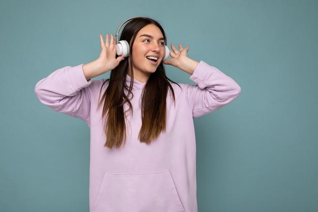 Schöne glücklich lächelnde junge brünette weibliche person mit hellviolettem hoodie isoliert über blauer hintergrundwand mit weißen bluetooth-headsets, die coole musik hört und zur seite schaut