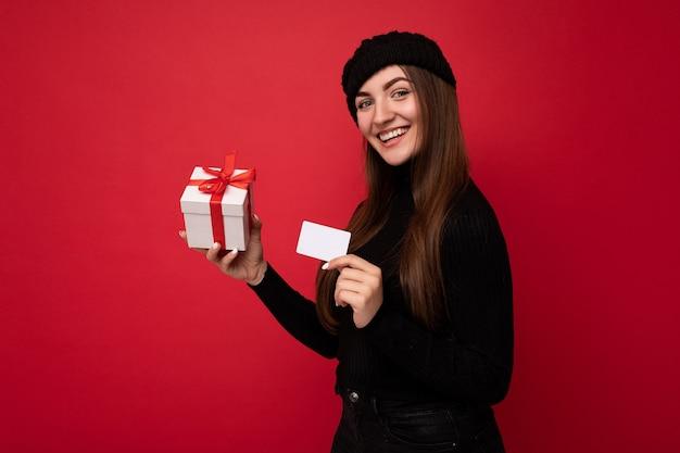 Schöne glücklich lächelnde sexy junge brünette frau mit schwarzem pullover und schwarzem hut isoliert auf rotem hintergrund mit kreditkarte und geschenkbox mit blick in die kamera