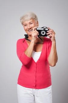 Schöne glückliche ältere frau, die foto durch retro-kamera nimmt