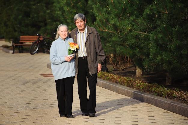 Schöne glückliche alte leute, die im frühlingspark gehen