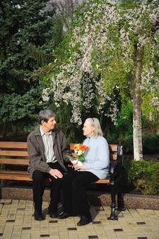 Schöne glückliche alte leute, die im frühlingspark sitzen