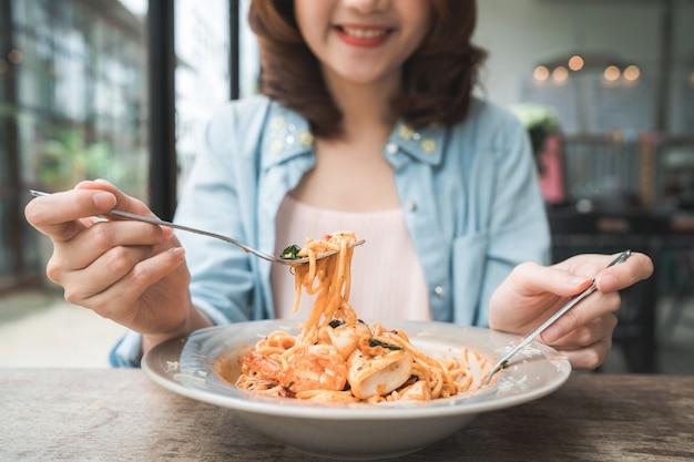 Schöne glückliche asiatische frau, die eine platte des italienischen meeresfrüchtespaghettis am restaurant oder am café während isst
