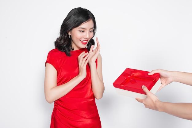 Schöne glückliche asiatische frau im roten kleid, die geschenkbox empfängt