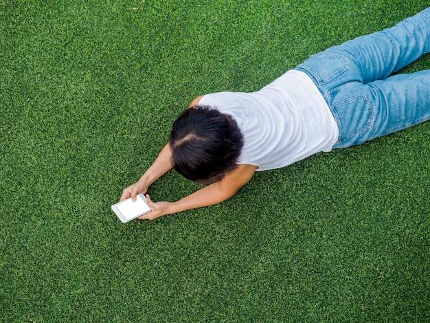 Schöne glückliche asiatische frau schwarzes kurzes haar in weißem ärmellosem hemd und blauer jeans, die mit dem lächeln auf das smartphone schaut, während sie auf grünem kunstrasen liegt, draufsicht.