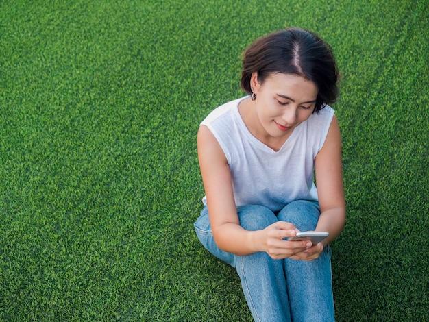 Schöne glückliche asiatische frau schwarzes kurzes haar in weißem ärmellosem hemd und blauer jeans mit blick auf smartphone mit lächeln beim sitzen auf grünem kunstrasen mit kopierraum, draufsicht