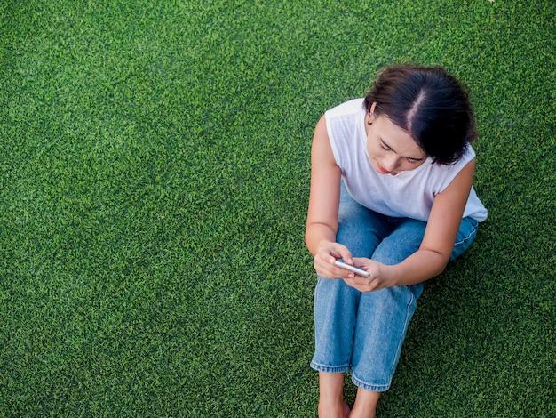 Schöne glückliche asiatische frau schwarzes kurzes haar in weißem ärmellosem hemd und blauer jeans mit handy mit lächeln beim sitzen auf grünem kunstrasen mit kopienraum, draufsicht.