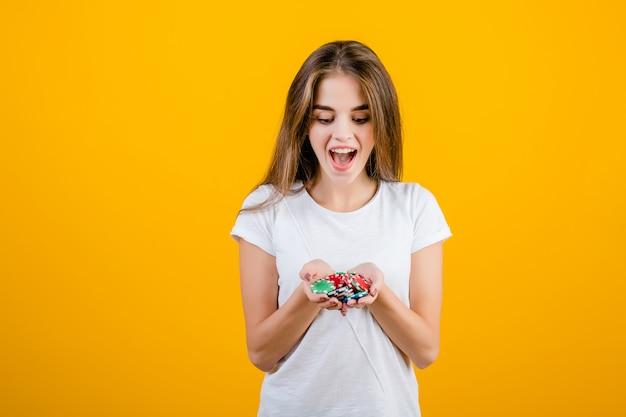 Schöne glückliche aufgeregte brunettefrau mit handvoll schürhakenchips vom on-line-kasino getrennt über gelb