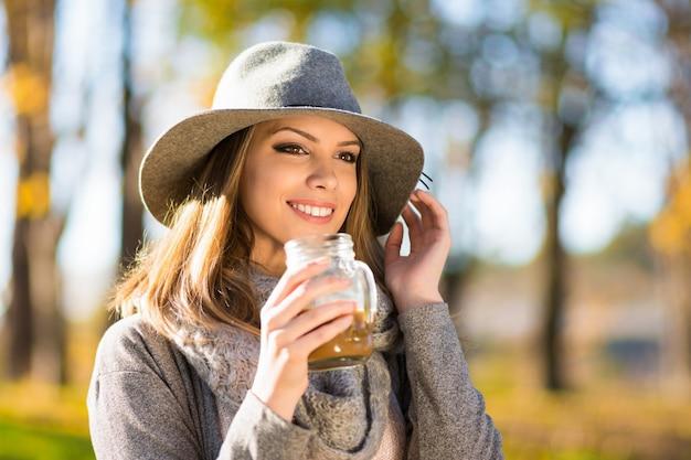 Schöne glückliche blonde junge frau in der grauen jacke und im hut