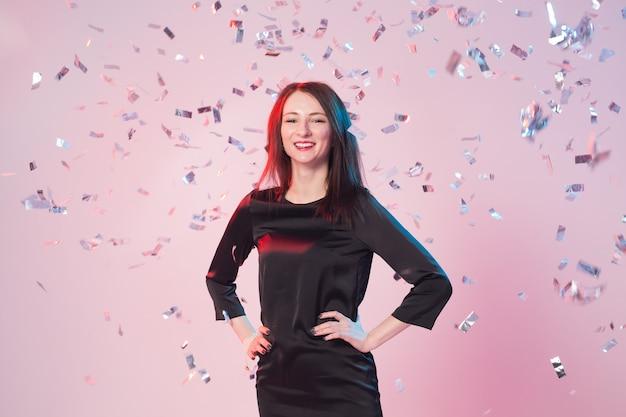 Schöne glückliche brünette frau, die mit fallendem konfetti lächelt und aufwirft. partykonzept