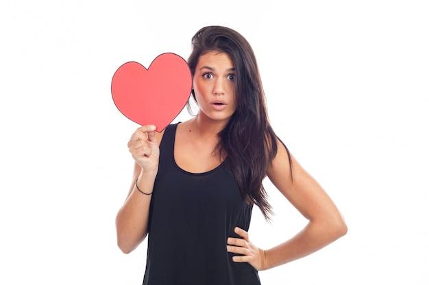 Schöne glückliche brunettefrau, die ein großes rotes herz hält und zeigt
