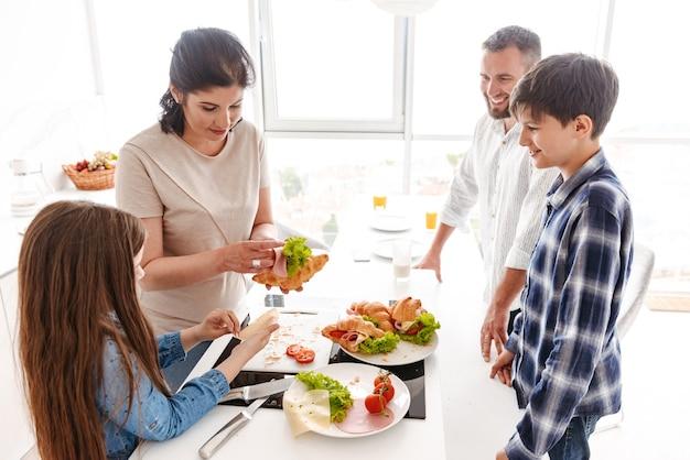 Schöne glückliche europäische eltern mit kindern 8-10, die zusammen in der hellen küche zu hause frühstücken und croissant-sandwiches essen