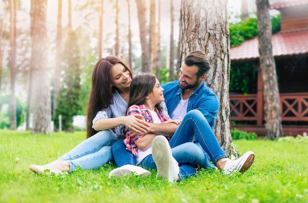 Schöne glückliche familie beim zusammensitzen im gras und beim umarmen