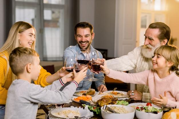 Schöne glückliche familie, die gläser wein und saft am feiertagsdinner klirrt