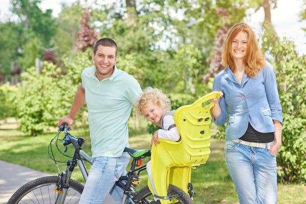 Schöne glückliche familie, die im park mit einem kind im babyfahrradsitz radelt und zeit zusammen verbringt.