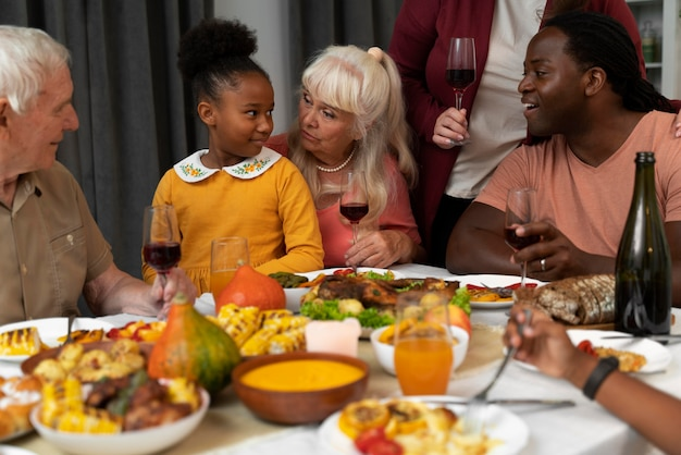 Schöne glückliche familie, die zusammen ein thanksgiving-dinner isst