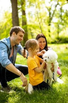 Schöne glückliche familie hat spaß mit bichon hund draußen im park