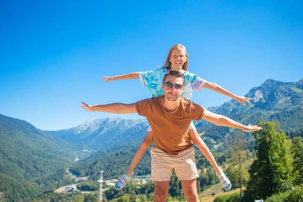 Schöne glückliche familie in den bergen im hintergrund
