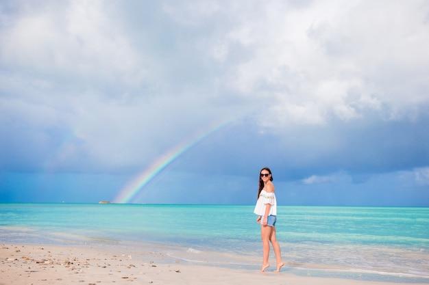 Schöne glückliche frau am strand mit schönen regenbogen über dem meer
