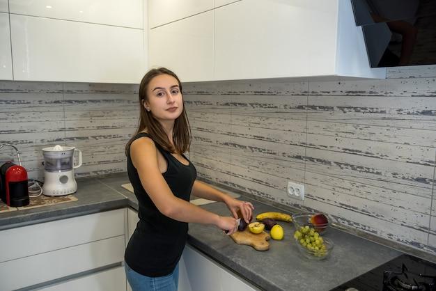Schöne glückliche frau auf küche, die obstsalat macht. konzept der gesunden ernährung